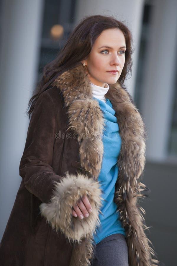 Femme dans le manteau de fourrure marchant sur la rue photo stock