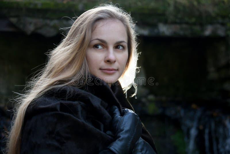 Femme dans le manteau de fourrure noir photo stock