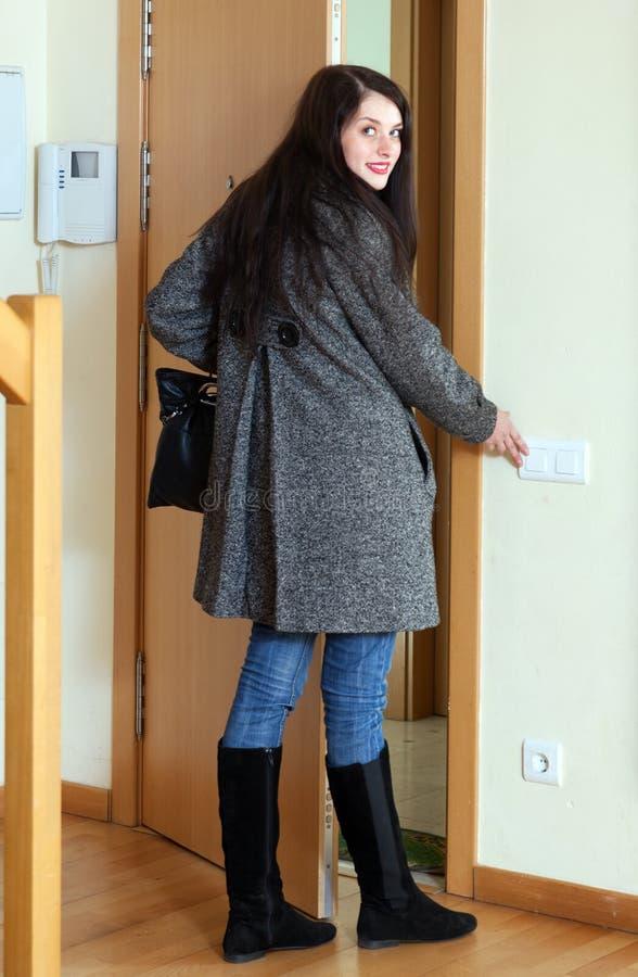 Femme dans le manteau quittant la maison image libre de droits