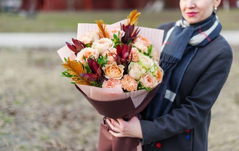 Femme dans le manteau tenant dans des ses mains un beau bouquet des fleurs roses tendres en emballage de papier photographie stock