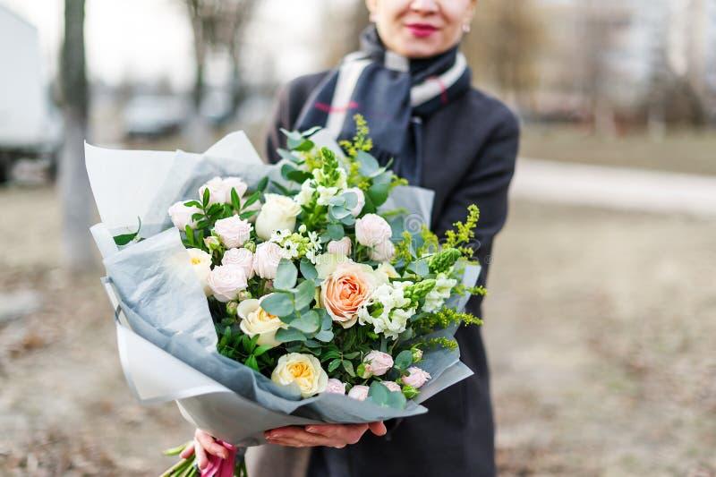 Femme dans le manteau tenant dans des ses mains un bouquet ?norme des fleurs roses tendres d?cor?es des feuilles vertes photographie stock