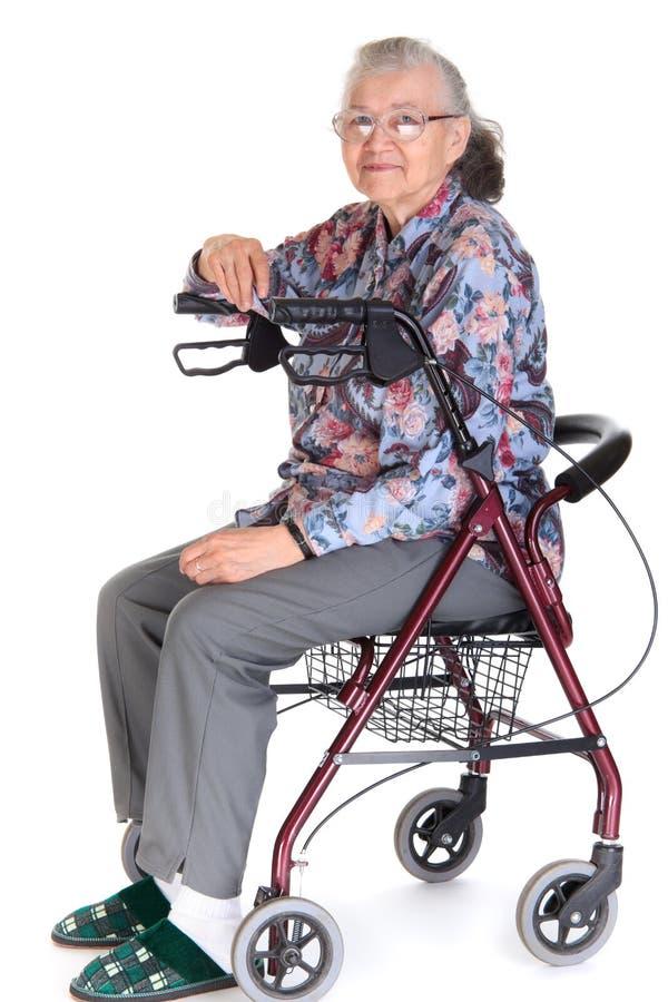 Femme dans le marcheur/fauteuil roulant images stock
