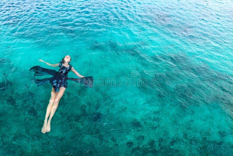 Femme dans le mensonge de détente de robe sur l'eau photographie stock libre de droits
