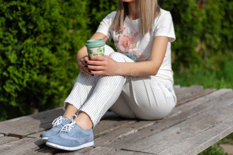 Femme dans le pantalon rayé, les espadrilles bleues et le T-shirt se reposant sur le banc et tenant la tasse de café et de repos photos stock