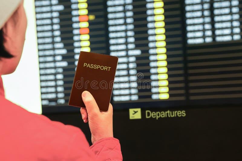Femme dans le passeport de participation d'aéroport, regardant le conseil de l'information de vol photographie stock libre de droits