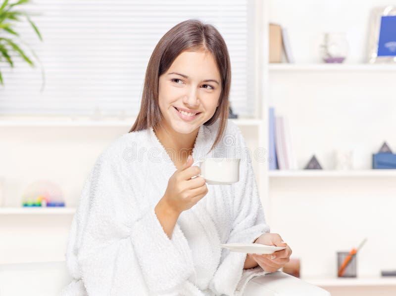 Femme dans le peignoir détendant à la maison photo stock