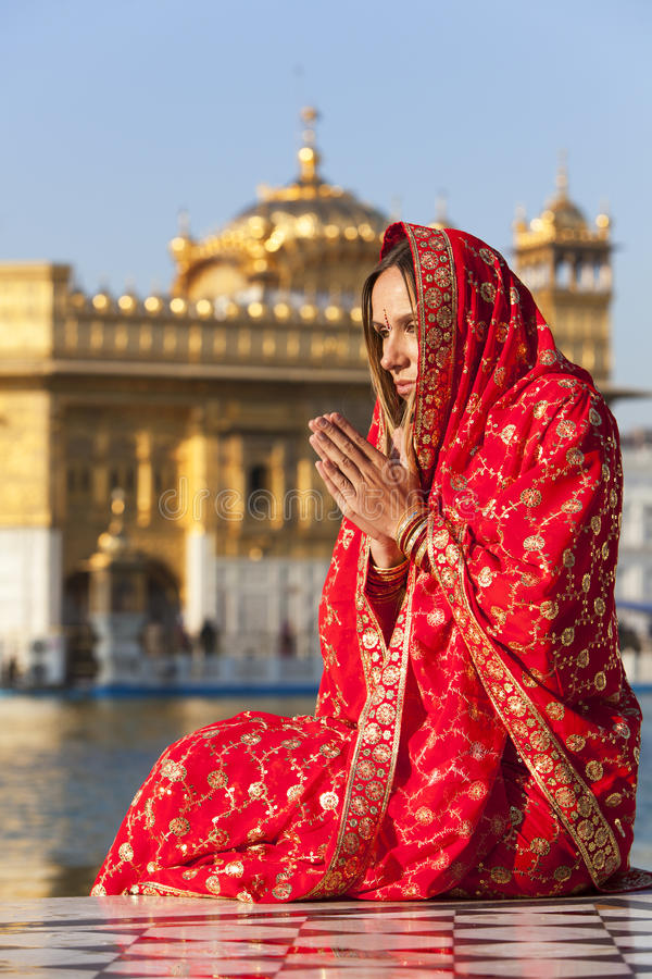Femme dans le sari rouge priant au temple d'or. photographie stock