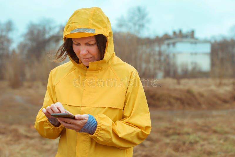 Femme dans le service de mini-messages jaune d'imperm?able au t?l?phone portable dehors photographie stock