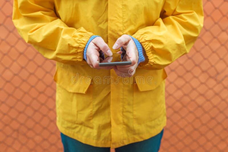 Femme dans le service de mini-messages jaune d'imperm?able au t?l?phone portable dehors images stock