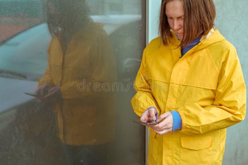 Femme dans le service de mini-messages jaune d'imperm?able au t?l?phone portable dehors photos libres de droits