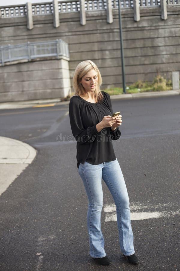 Femme dans le service de mini-messages supérieur noir au téléphone portable photo libre de droits