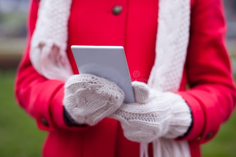 Femme dans le Smart-téléphone de prise de gants de laine photos stock