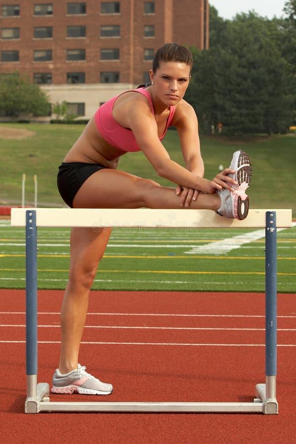 Femme dans le soutien-gorge de sports et circuits étirant le tendon du jarret sur l'obstacle images stock