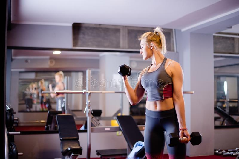 Femme dans le sport de gymnase s'exerçant avec des poids photographie stock