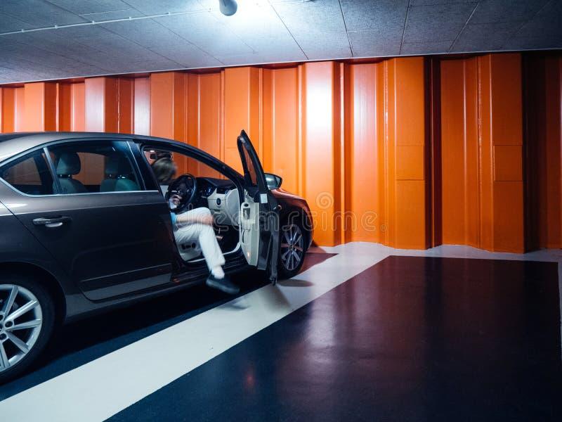 Femme dans le stationnement souterrain avec la voiture de Skoda Octavia photo stock