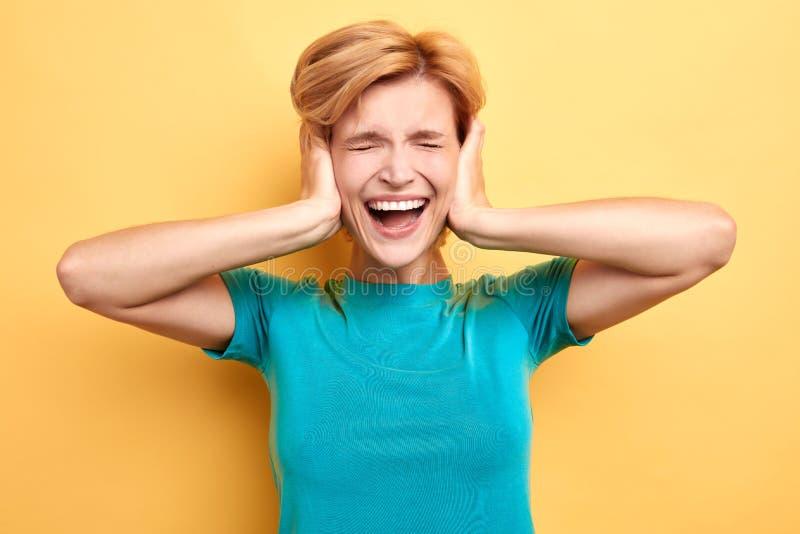 Femme dans le T-shirt bleu avec les yeux fermés posant à la caméra photographie stock libre de droits