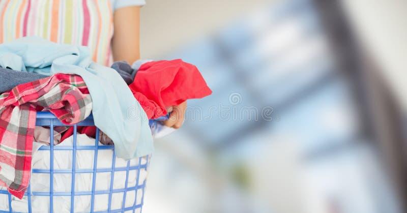 Femme dans le tablier avec la blanchisserie contre la fenêtre trouble image stock