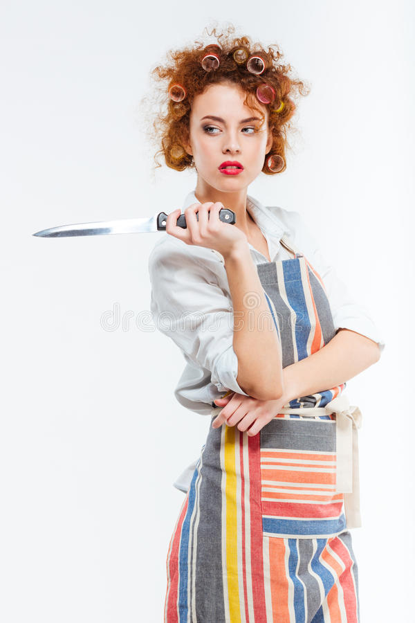 Femme dans le tablier tenant le couteau photos stock