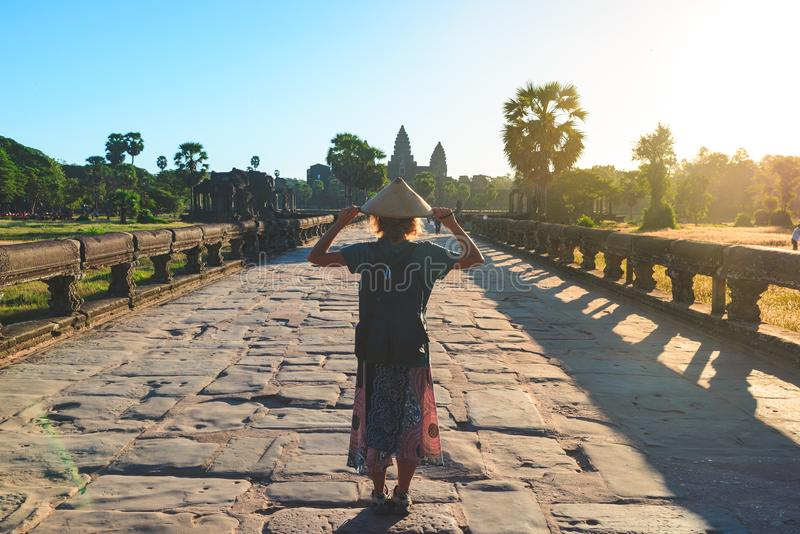 Femme dans le temple de Bayon regardant les visages en pierre, Angkor Thom, ciel bleu clair de lumi?re de matin Concept de m?dita photos libres de droits