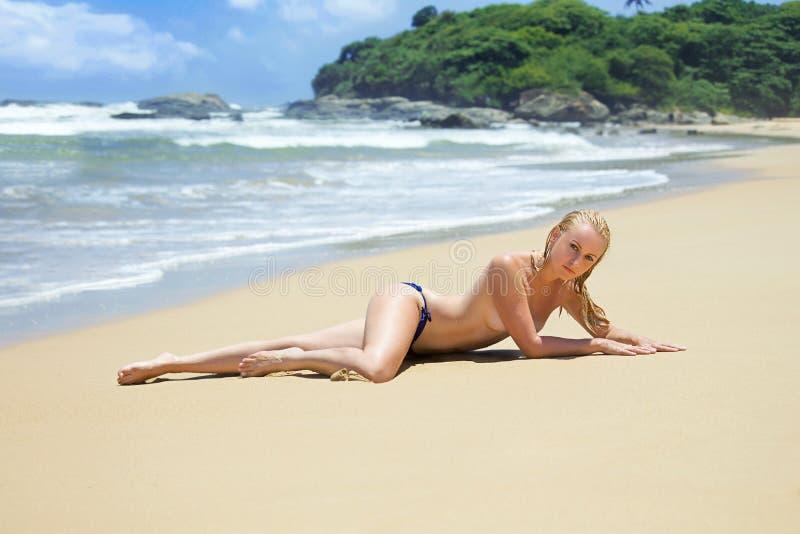 Femme dans le torse nu de bikini sur la plage isolée images libres de droits