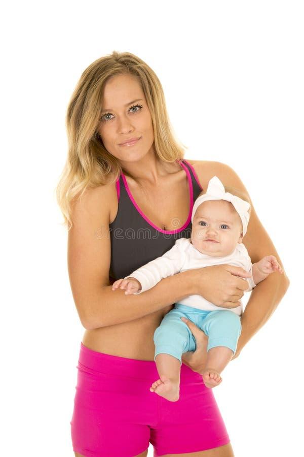 Femme dans le vêtement de forme physique se tenant avec le bébé images stock