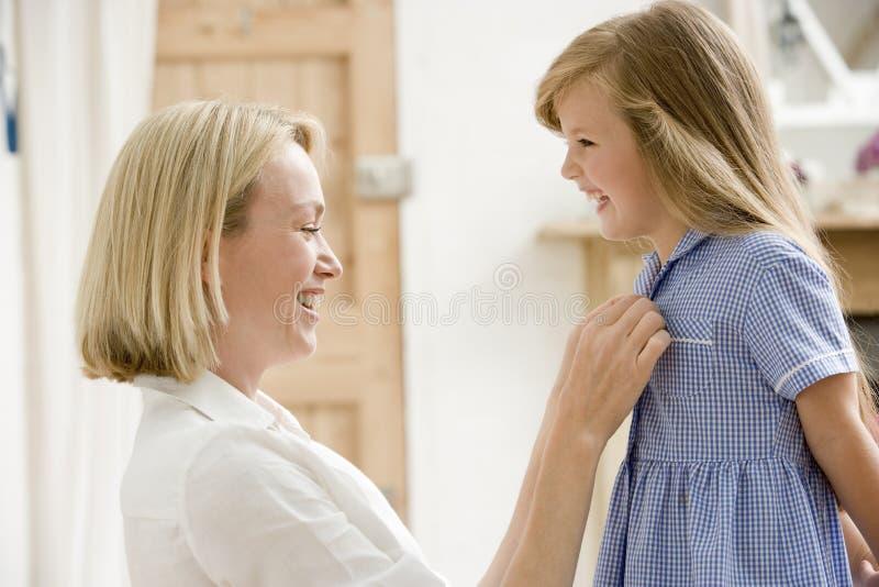 Femme dans le vestibule avant fixant la robe a de jeune fille photographie stock