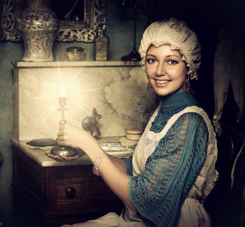 Femme dans le vieux capuchon avec le chandelier image stock