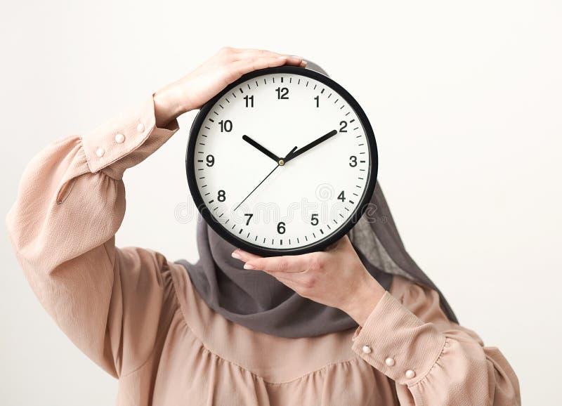 Femme dans le visage de bâche de hijab avec l'horloge photos stock