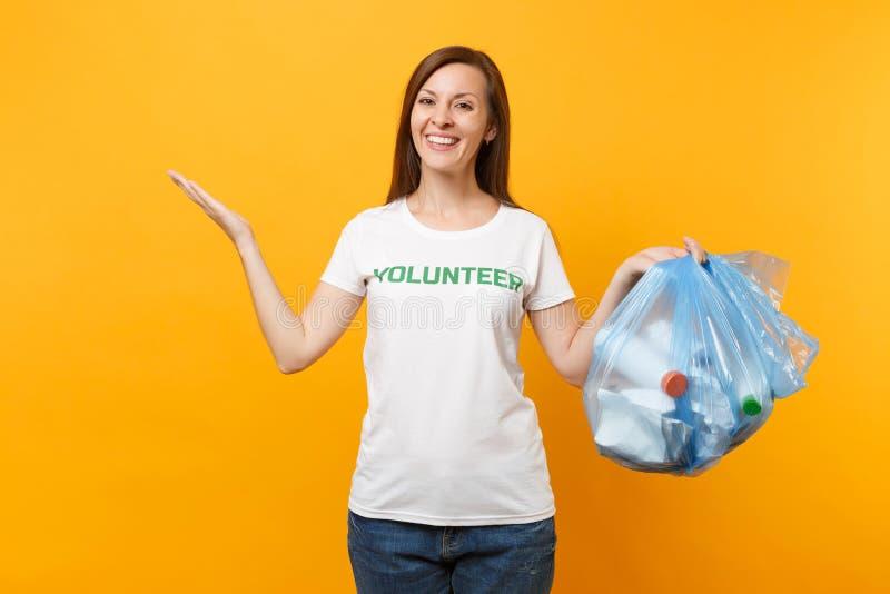 Femme dans le volontaire de T-shirt, sac de déchets d'isolement sur le fond jaune Aide libre volontaire d'aide, grâce de charité photos libres de droits