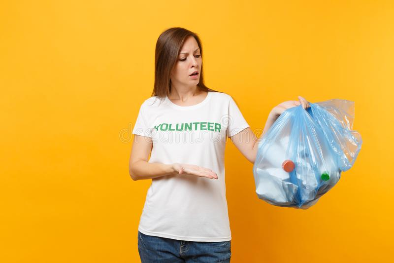 Femme dans le volontaire de T-shirt, sac de déchets d'isolement sur le fond jaune Aide libre volontaire d'aide, grâce de charité photo stock