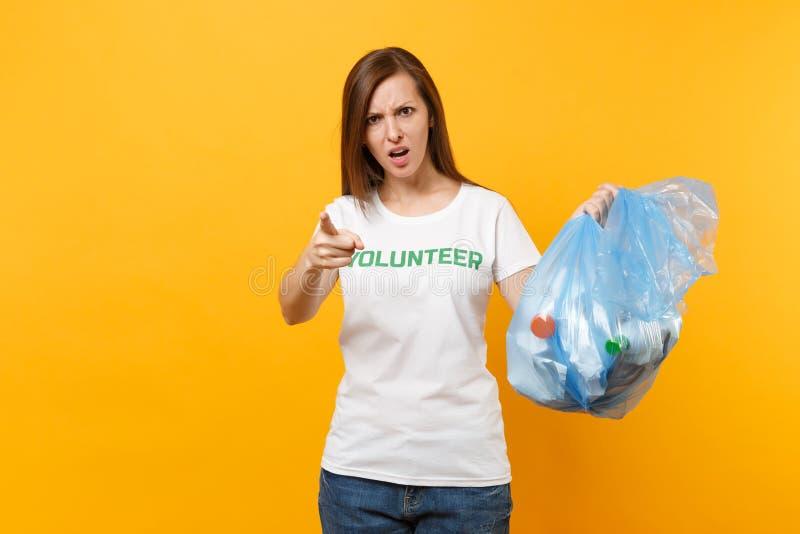 Femme dans le volontaire de T-shirt, sac de déchets d'isolement sur le fond jaune Aide libre volontaire d'aide, grâce de charité images libres de droits