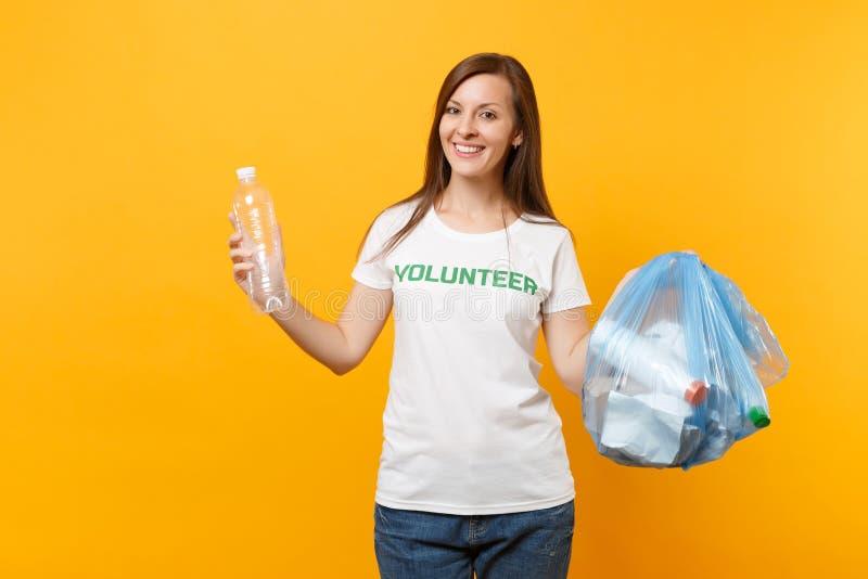 Femme dans le volontaire de T-shirt, sac de déchets d'isolement sur le fond jaune Aide libre volontaire d'aide, grâce de charité image libre de droits