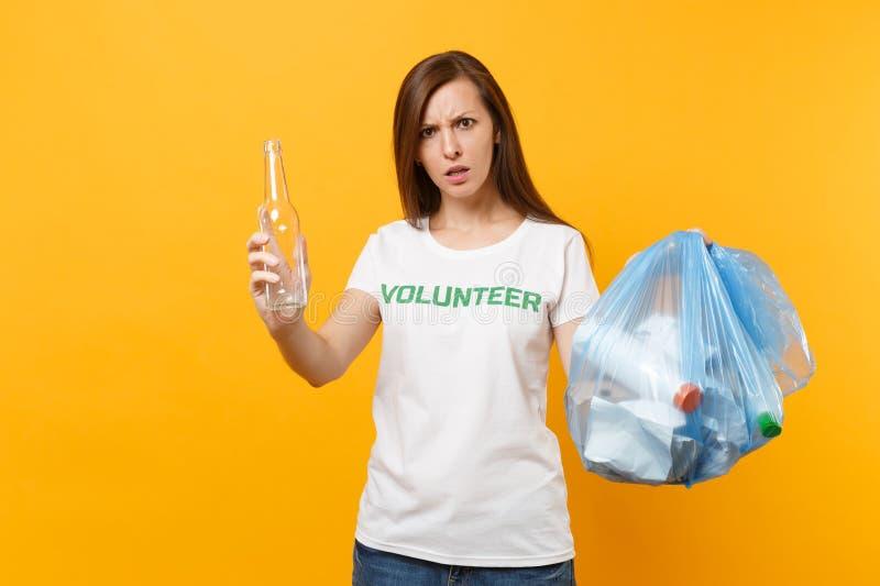 Femme dans le volontaire de T-shirt, sac de déchets d'isolement sur le fond jaune Aide libre volontaire d'aide, grâce de charité images stock