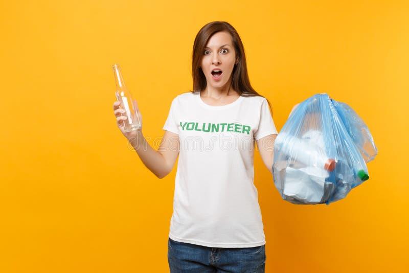 Femme dans le volontaire de T-shirt, sac de déchets d'isolement sur le fond jaune Aide libre volontaire d'aide, grâce de charité photos stock