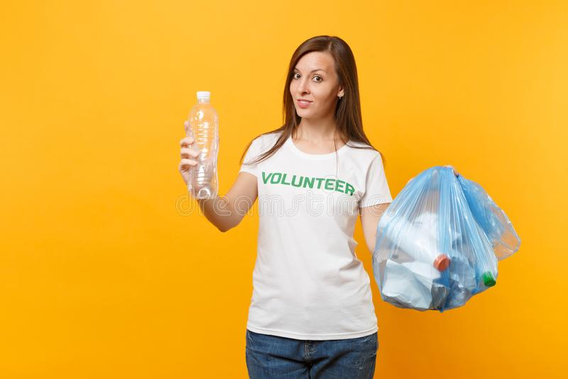 Femme dans le volontaire de T-shirt, sac de déchets d'isolement sur le fond jaune Aide libre volontaire d'aide, grâce de charité photographie stock