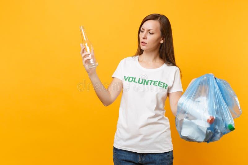 Femme dans le volontaire de T-shirt, sac de déchets d'isolement sur le fond jaune Aide libre volontaire d'aide, grâce de charité photo libre de droits