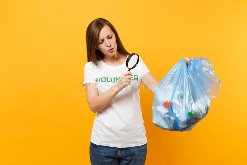 Femme dans le volontaire de T-shirt, sac de déchets d'isolement sur le fond jaune Aide libre volontaire d'aide, grâce de charité photographie stock libre de droits