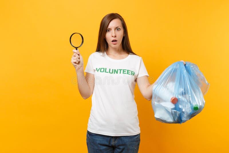 Femme dans le volontaire de T-shirt, sac de déchets d'isolement sur le fond jaune Aide libre volontaire d'aide, grâce de charité image stock