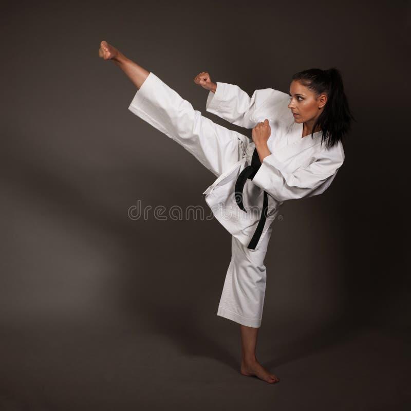 Femme dans les éruptions blanches de kimono hautes dans le ciel - une fille d'art martial de karaté image stock