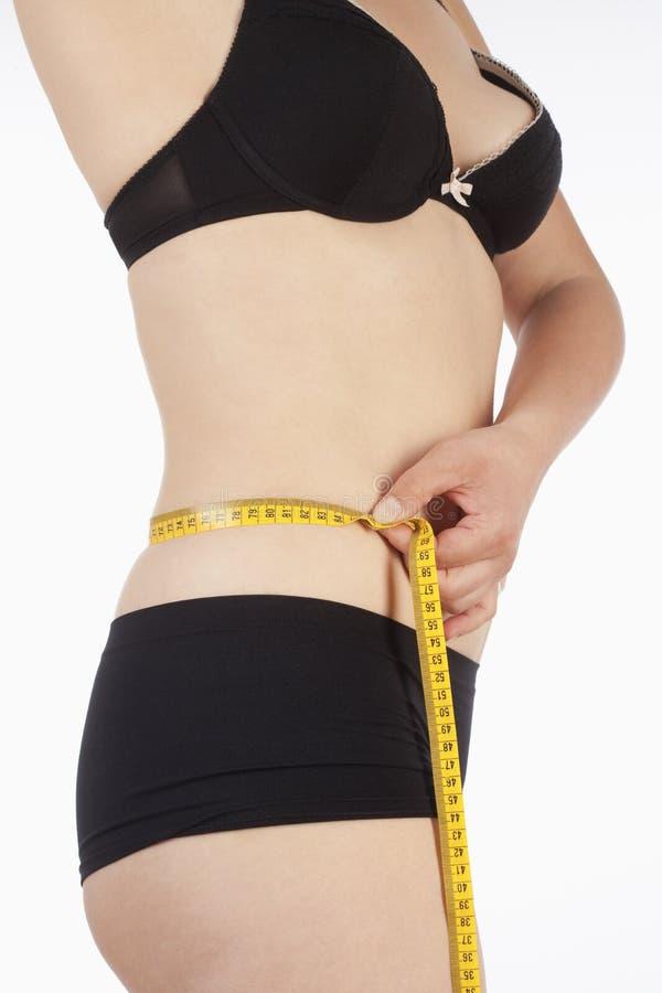 Femme dans les sous-vêtements mesurant sa taille photos libres de droits
