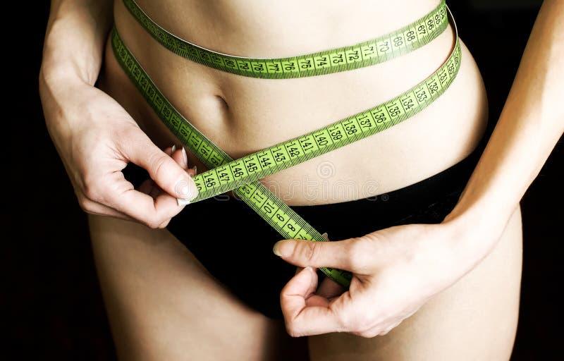 Femme dans les sous-vêtements noirs mesurant la taille images stock