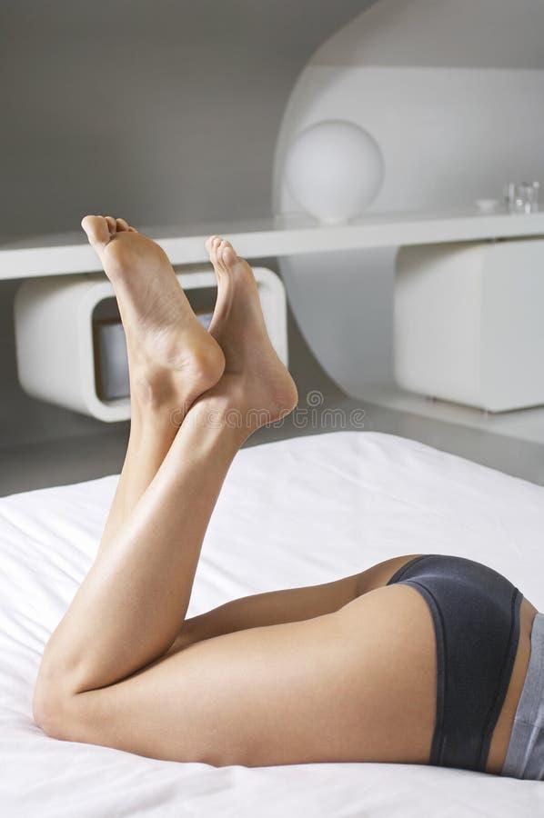 Femme dans les sous-vêtements se situant dans le lit photographie stock