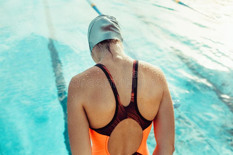 Femme dans les vêtements de bain pratiquant dans la piscine photo libre de droits