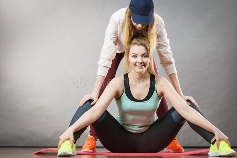Femme dans les vêtements de sport étirant des jambes avec l'entraîneur photo libre de droits