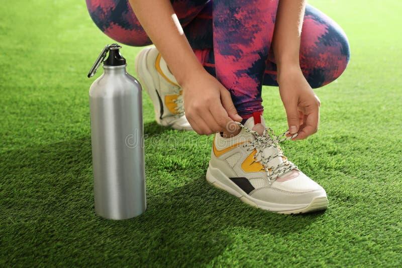 Femme dans les vêtements de sport avec la bouteille de la chaussure de laçage de l'eau photos libres de droits