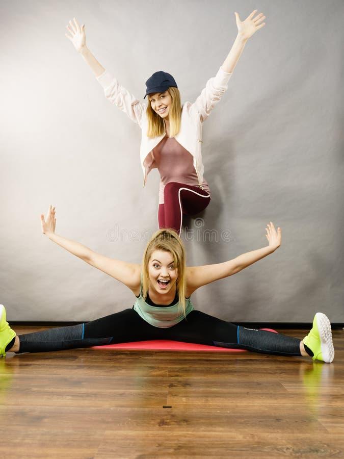 Femme dans les vêtements de sport faisant la séance d'entraînement avec l'entraîneur image stock