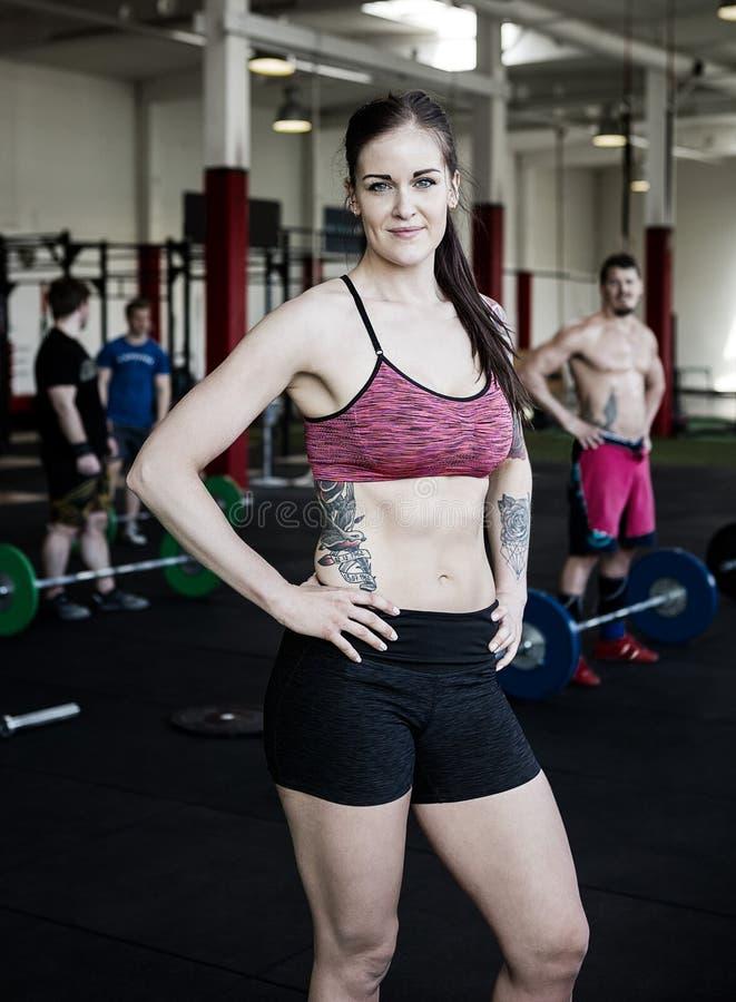 Femme dans les vêtements de sport se tenant avec des mains sur des hanches dans le gymnase photographie stock libre de droits