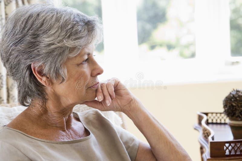 Femme dans penser de salle de séjour photos stock