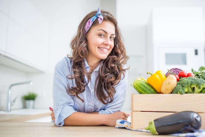 Femme dans sa cuisine avec la boîte en bois complètement du légume organique photo libre de droits