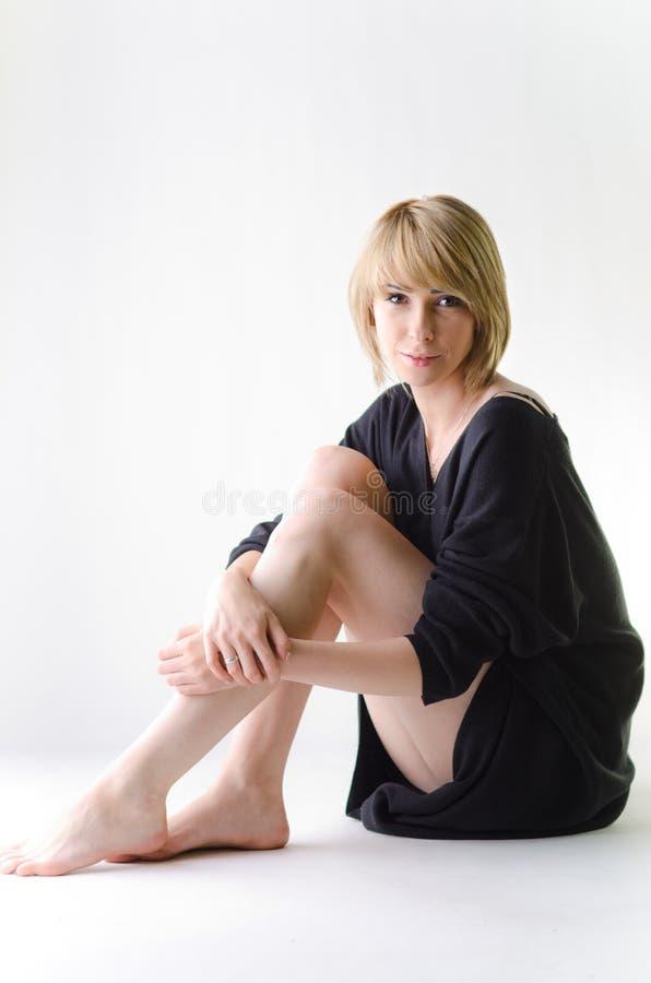 Femme dans un chandail noir lâche et grand se reposant en longueur photographie stock